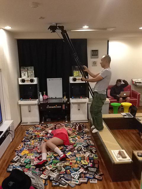 レトロゲームのコレクターのロケ風景。撮影スタジオではないので、カメラマンはこんな曲芸のような撮影を敢行したりしているのです。