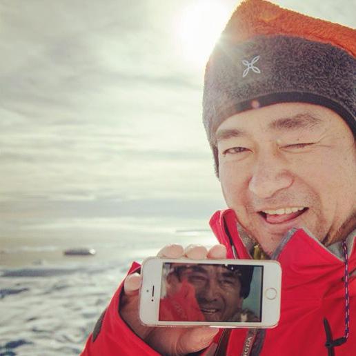 南極初上陸時のニヤけた写真。iPhoneの待ち受けに期間限定で設定しておいた「南極物語」の健さんと共に。でも南極物語のブリザードな世界とは違って穏やかな天気でした。