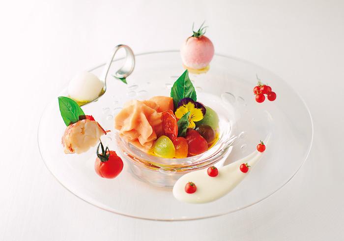 """ランチコース¥5,000(税込み、ほかパン代¥540)の""""選べる4皿""""の前菜として春から夏にかけ登場。日本各地から取り寄せた15種類の有機トマトを使用している。"""