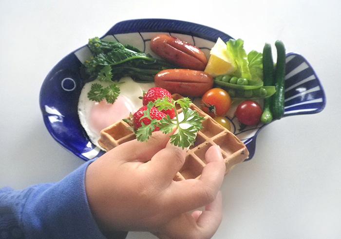 この日はワッフルと生野菜のサラダを弟、ソーセージと目玉焼き、スナックエンドウなど旬の野菜のボイルを兄が担当。手に持っているハーブは家庭菜園でとれたもの。