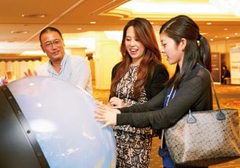 会場に設置された「触れる地球」。地球儀で仲良く遊ぶ、中井さんと盛田さん。