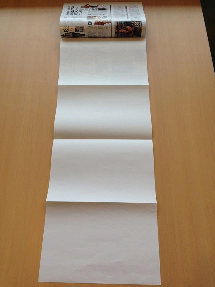 印刷所から届いたポスターの束見本。上の本誌サイズ1ページからパラ、パラ、パラ、と広がって……全長80cm強!