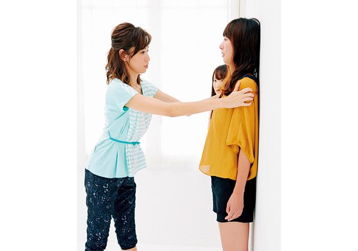 1. 姿勢をチェック 両足の親指とかかとをくっつけ、かかと、ふくらはぎ、ヒップ、肩甲骨、後頭部を壁につけて立つ。背中と壁の隙間に1.5枚分の手が入るかをチェック。2枚分以上空く人は腹筋に力をいれ、お腹と背中をつけるイメージでお腹を上に引き上げる。背中がS字になると◎
