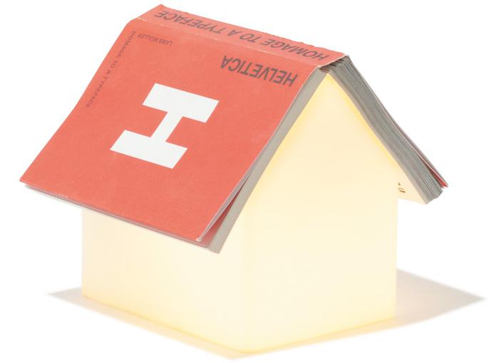 """読書タイムが楽しみになる""""家型""""ランプ。 読みかけの本を開いたままライトの上に置くと、まるで家の屋根のように見えるユニークなデザイン。すりガラス越しの光はやわらかく、本を読むのにも十分な明るさ。¥8,500(MoMAデザインストア☎03・5468・5801)※本はサンプル"""