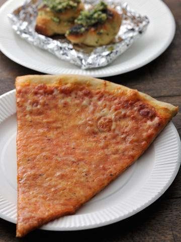 ペパロニスライス ¥500。アメリカンスタイルのピザは、持ち上げてもピンッとハリがありクリスピー! ガーリックナッツ ¥200は生地を丸めたスナック(共に税込み)。