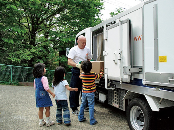 施設の子どもたちに食材を配るチャールズさん。米国の留学生として来日。隅田川べりでホームレスを15カ月体験し、活動を始めた。