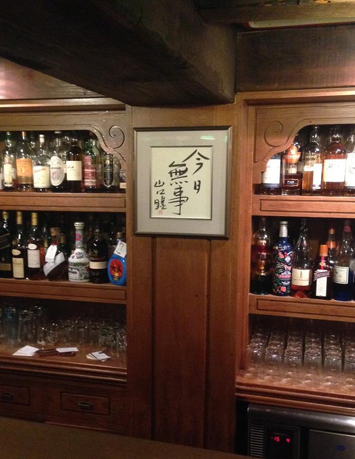 金沢片町のバー〈倫敦屋酒場〉のカウンターに飾られた山口瞳の「今日無事」。この言葉を眺めながらウィスキーを飲む。
