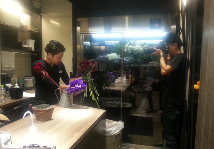 お花屋さんでの撮影にて。カメラマンさんもたまたま黒い服を着用。黒服男子職人の2乗という、贅沢な眺めです。