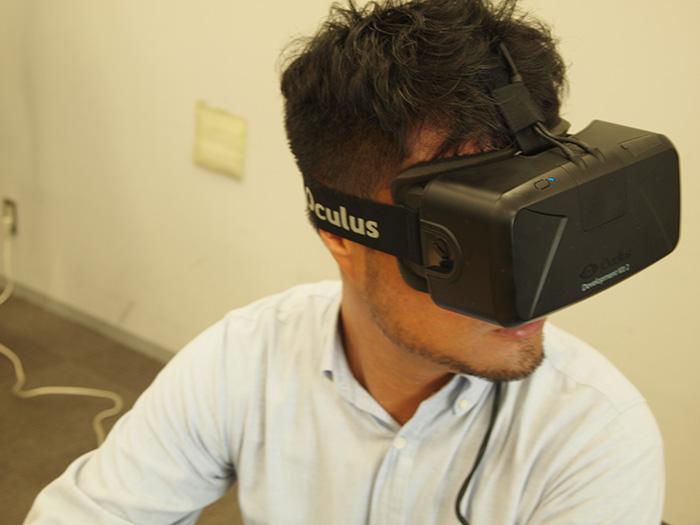 HMD(ヘッドマウントディスプレイ)の3D映像に合わせ、思わず横を向く副編集長杉江。