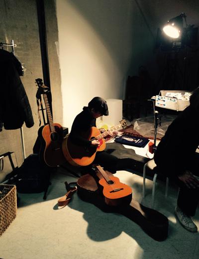 撮影を盛り上げるために現場には本物のギター弾きが。いや、ウソです、スタイリストの島津さんです。ジョニ・ミッチェルをテーマにしたこの撮影、ギターはすべて島津さんの私物でした。お宝級のギターも!