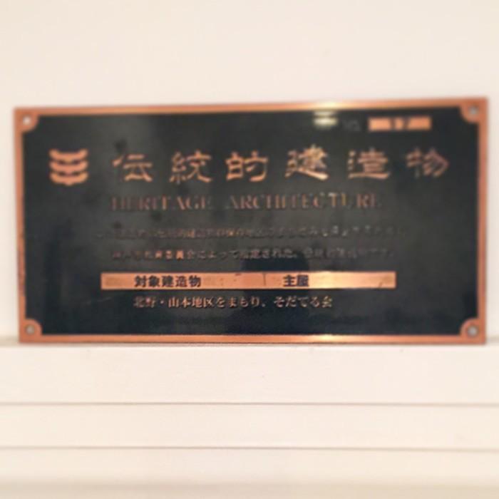 神戸の異人館に住む金子修一さんの家の中で見つけた『伝統的建造物』の証。購入には、外観を当時のままキープするなど、いくつかの条件があるという。赤茶色の鎧戸、扉の上にすえられたステンドグラス……、100年以上まえのものがいまも美しく保たれているのは、金子さんの日々のメンテナンスのおかげだ。