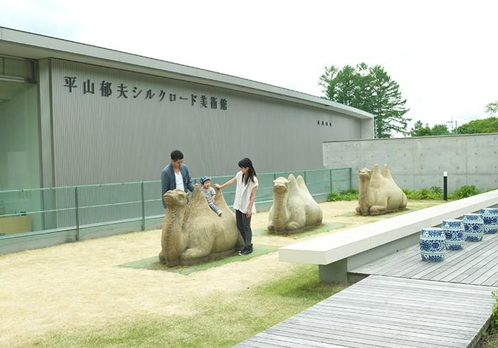 平山郁夫シルクロード美術館のらくだ公園でご両親と遊ぶ、喜之助くん(1歳8ヶ月)。初めての美術館(?)体験だそうです。撮影:若木信吾