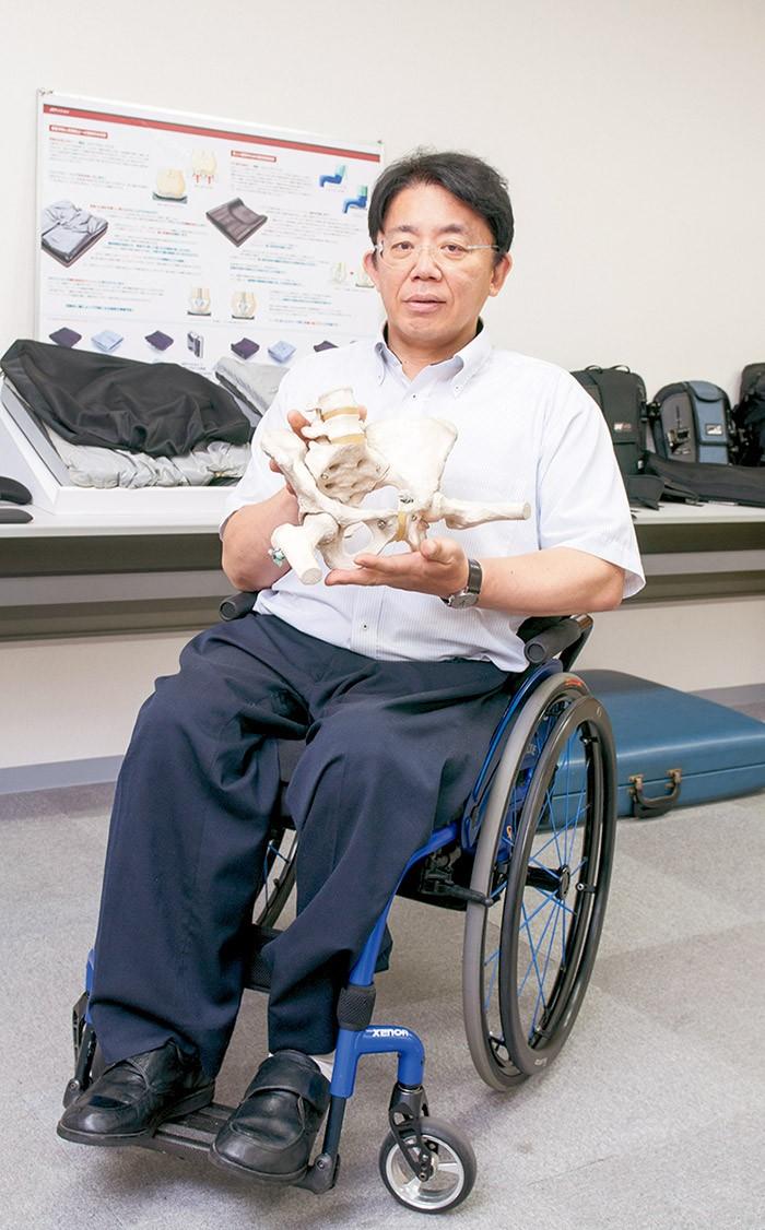 骨盤の模型を手に、シーティング用クッション(左奥)の重要性を語る山崎さん。社長業、講演、ダイビングと多忙な日々。