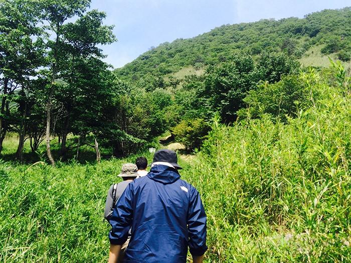 山に映える先輩編集者の青く大きな背中。偉大な男の背中は決まって広い!