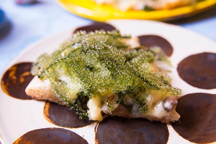 沖縄から仕入れている旬の食材をふんだんに使った料理。前菜は、いろいろな味を一口ずつ楽しめるのが魅力。次に登場したのは迫力のビジュアル、海ぶどうのピザ。料理だけでなく、沖縄の器を使ったテーブルコーディネートも自慢。