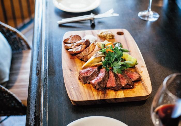 """赤身の牛肉は""""水のように""""のど越しの良いしっとり焼き。逆に豚は表面に少しカリカリ香ばしさを。「塊で焼いたほうが絶対おいしい」と田中シェフ。写真で3~4名分。肉と野菜で¥5,400前後。"""