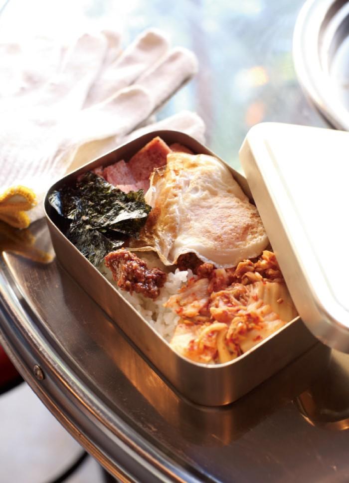 キムチ、目玉焼き、スパム、韓国海苔、サムジャンがアルミ製弁当箱に入った思い出の弁当500円は「振って振って振ってから食べてください」。カバンの中で思いきり揺すられたように中の具材が混じり、ビビンバ状態に。