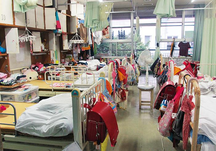 ある児童養護施設の女子小学生の8人部屋。個人の空間はベッドの上だけ。プライバシーを保つのはベッド間の薄いカーテン。