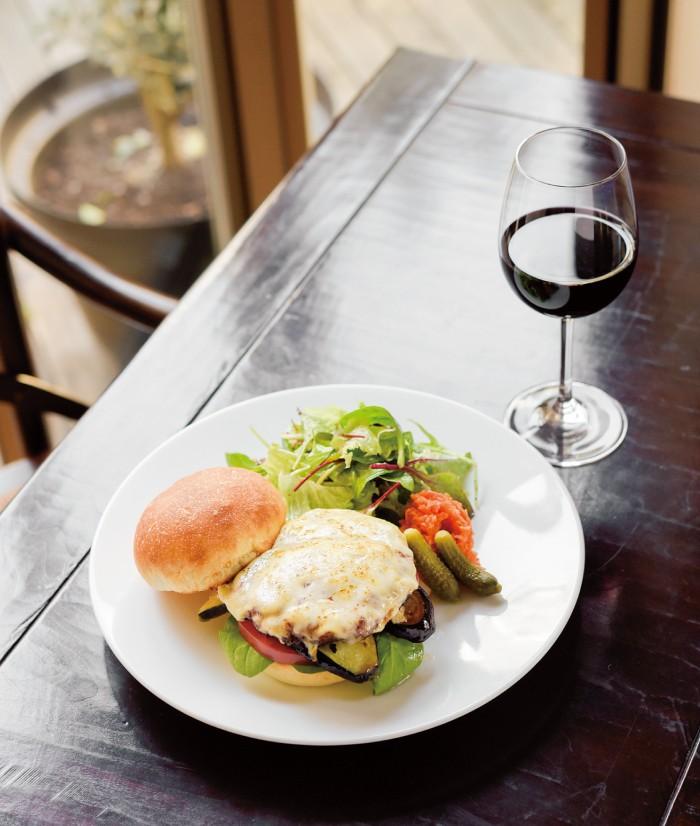 ティアラス特製ラムのハンバーガー1200円、ランチドリンクのグラスワイン300円。グリュイエールとゴーダチーズに150gのパテ、フレッシュトマト、茄子のローストをもっちりバンズでサンド。バンズは代々木上原のカタネベーカリー特製。たっぷりの野菜がうれしい。