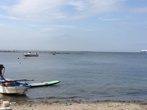 目の前は遠浅の海。水平線近くにゆったりと進む客船も。手前の船にはカサゴやメバルを獲る網が。