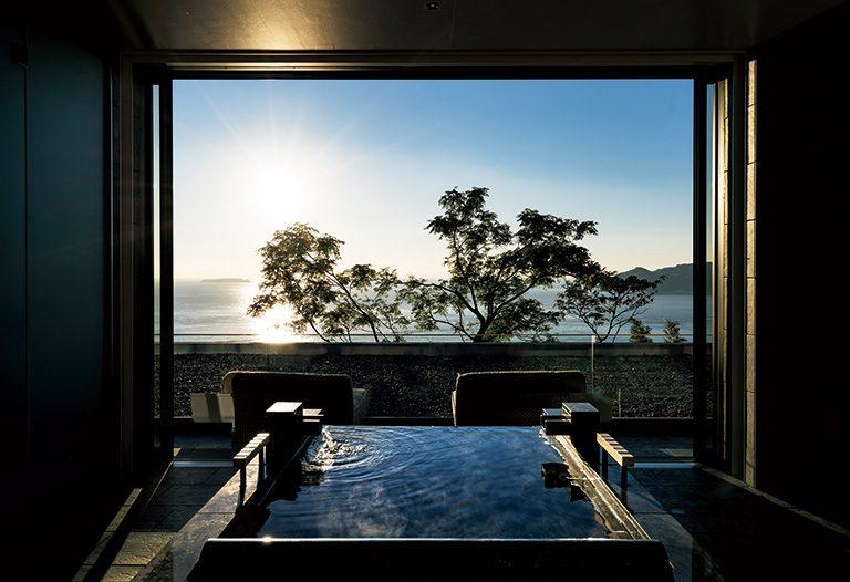 客室内のお風呂から全面に広がる海と朝日を望む。