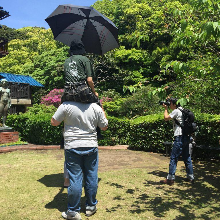 あまりに晴れて日差しが強すぎたため、肩車で高さを作って傘をさして影を作っているの図。
