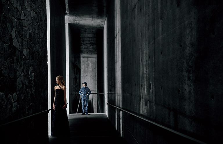 コンクリートと坡州石の壁面が対峙する天井を高くとった廊下は、奥行きのある圧倒的なスケール感を作り出す。